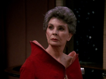 Screencap of Jean Simmons as Norah Satie: an elegant woman in her early 60s with short, dark grey hair, wearing a red gown with an asymmetric vertical collar.